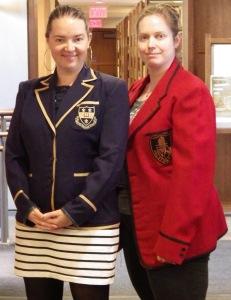 Two staff members model blazers